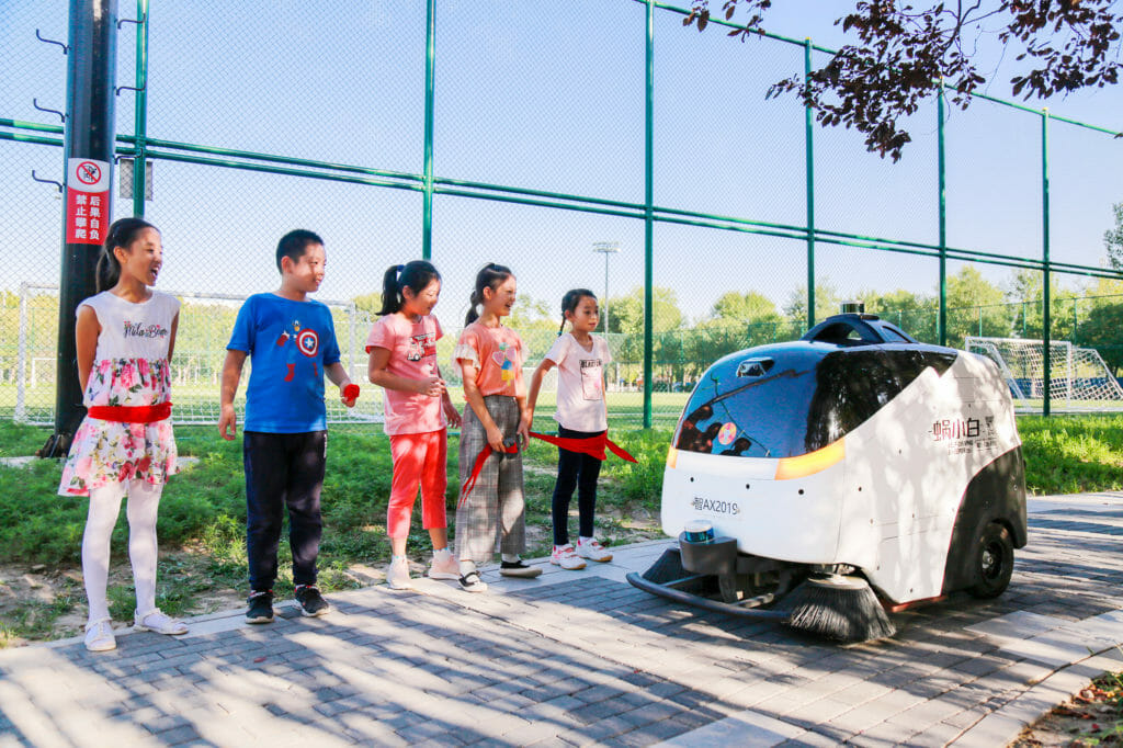 Idriverplus WOXIAOBAI, equipped with two Velodyne Puck sensors, safely navigates and cleans streets in China with children looking on
