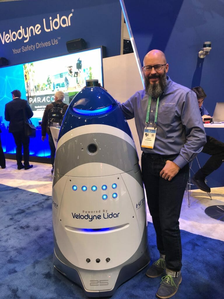 Webinar guest Stacy Stephens (EVP and Chief Client Officer at Knightscope) with a Knightscope security robot at Velodyne's CES booth