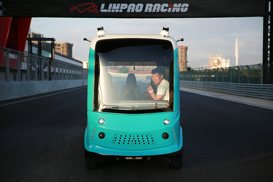 TURING Drive's 4-meter OPAL Shuttle With Velodyne Puck lidar sensors driving on a racetrack with passengers